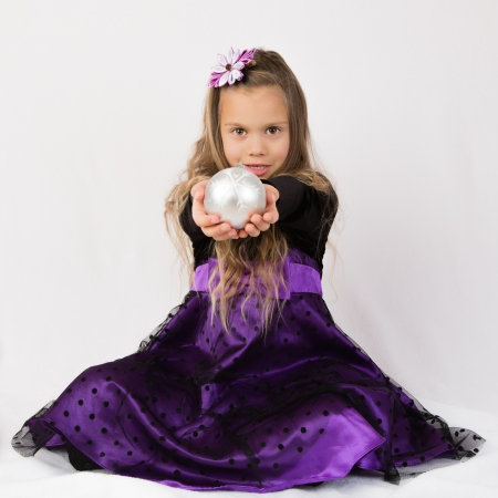 kanzashi: A beautiful  girl in purple dress, wearing head decorations handing a christmas tree decoration Stock Photo