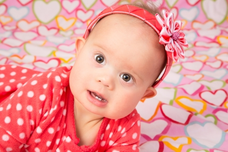 blanked: An adorable baby girl wearing a red headband with a decorative flower, lying on a blanked with hearts Stock Photo