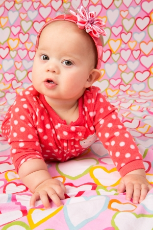 kanzashi: An adorable baby girl wearing a red headband with a decorative flower, lying on a blanket with hearts design printed on it Stock Photo