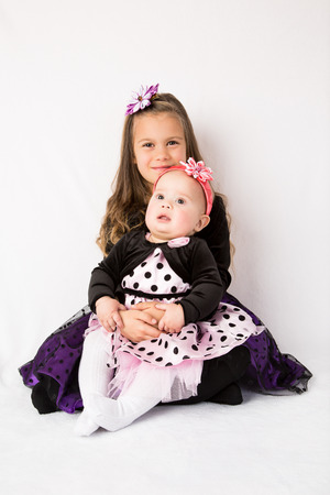 kanzashi: Two sisters  6 years old and 6 months old wearing beautiful dresses and head decorations, sitting against white fluffy background Stock Photo