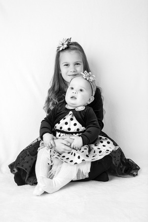 kanzashi: Two sisters  6 years old and 6 months old wearing beautiful dresses and head decorations, sitting against white fluffy background  Styled as high contrast black and white  Stock Photo