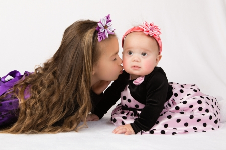 kanzashi: A six years old girl kisses her baby sister in a cheek, while lying on a white surface against white fluffy background