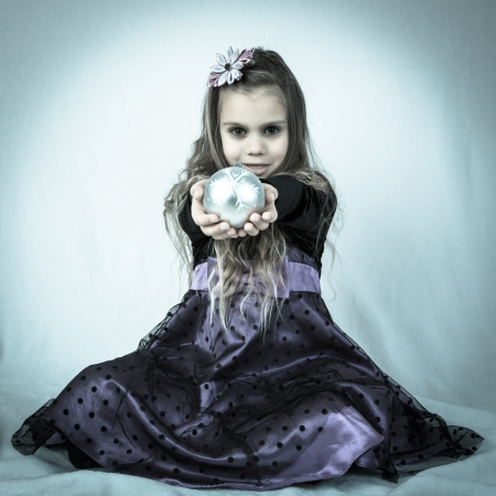 kanzashi: A beautiful  girl in purple dress and with head decorations handing out a christmas tree decoration  Styled in cold high contrast  bluish-grey evil tones  Stock Photo