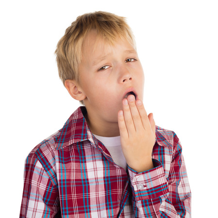 Bored young boy yawning, isolated