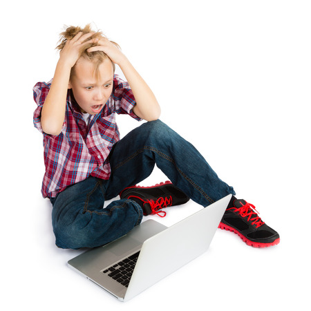 A shocked pre-teen boy with tousled hair sitting in front of  a laptop computer, looking at its screen with awe and terror