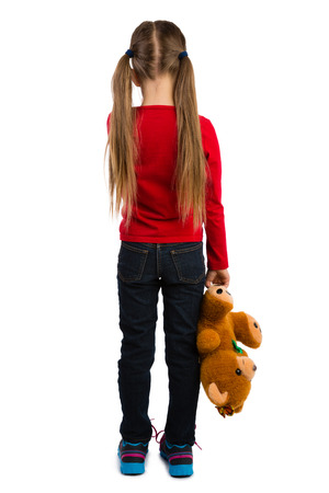 Girl stands with her back to the viewer,  holding a teddy bear