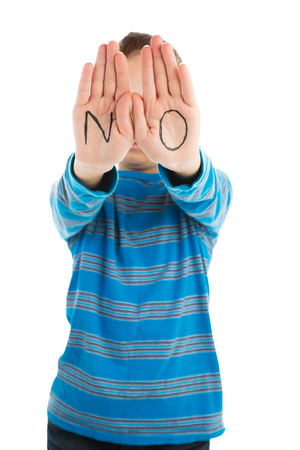 Pre-teen boys displays word  NO  written on his palms