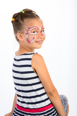 Smiling Girl With Abstract  Face Painting Looking Over Her Shoulder, Isolated photo