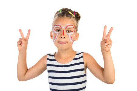 Little girl with an abstract paint on her face , showing her tongue and a victory sign with both hands, isolated photo
