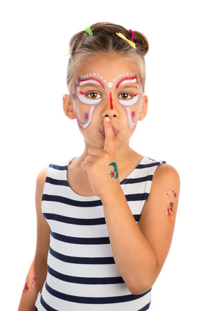 Little girl with abstract face painting holding an index finger against her lips, isolated Stock Photo