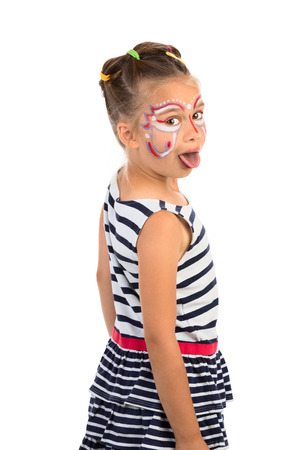 Little girl with an abstract paint on her face looking over her shoulder and showing her tongue, isolated photo