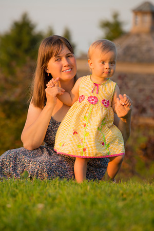 Baby girl with her mother in summer park in the evening photo