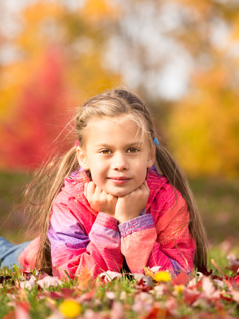 A front portrait of a little girl lying on a colorful leaves in autumn park photo