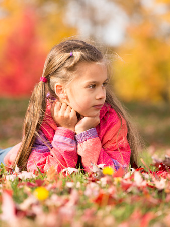 Little girl lying on a colorful leaves in autumn park
