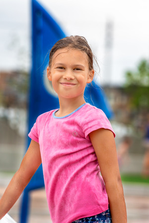A school-aged girl wearing a wet t-shirt at a splash playground Stock Photo