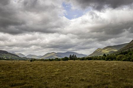 A simple landscape with dry brown grassy foreground and mountains and lots of clouds Фото со стока