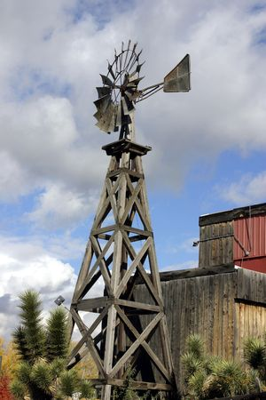 Old Wooden Windmill with Clouds on teh Background