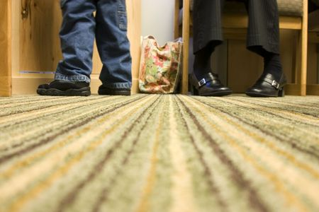 Floor Level Shot of Mom and Son - shoes and feet on the carpet photo