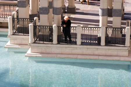Lone Gondolier Looking At the Water by the Dock photo