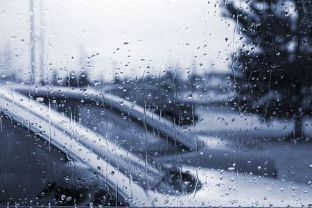 inclement weather: Rain on the Windshield with the parked cars on the Background