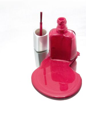 Isolated Nail Polish Spilling on a Mirror with the Brush Standing