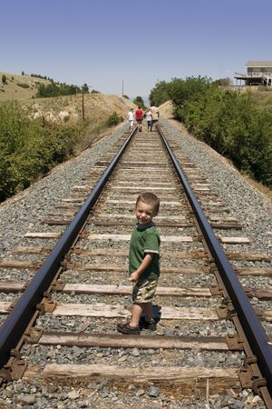 Little Boy Looking at the Camera on the Train Tracks Stock Photo - 533347