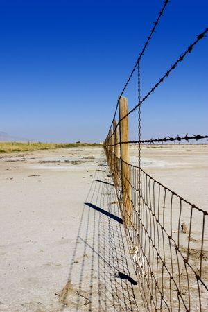 Fence in the Salt Lake in Summer in Utah with Clear Blue Skies Stock Photo