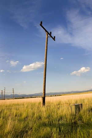 Electric Pole in a Field in Helena Montana with Blue Skies and Clouds on the Background Stock Photo - 950115