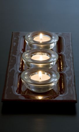 Three lit candles in a row photo