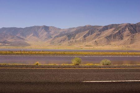 Snelweg met bergen op de achtergrond en een stream tussen de rijstroken Stockfoto