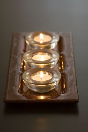 tibet bowls: Three lit candles in a row Stock Photo