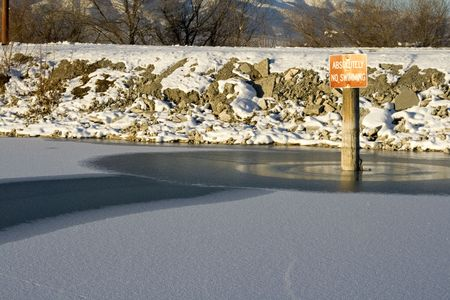 No Swimming Sign on the Frozen Lake in Winter Stock Photo - 2303267