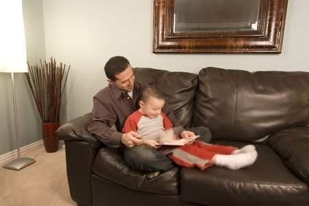 Father is reading a book to his hyper son moving around photo