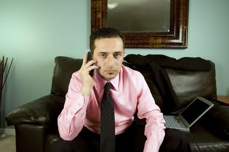 Businessman Talking on the Phone Sitting on the Couch Looking at the Camera Stock Photo - 2570769