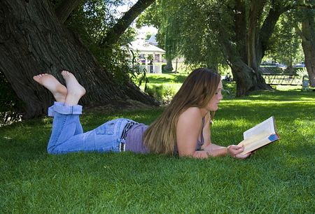 Close up on a Beautiful Girl Laying Down in the Park Reading a Book photo