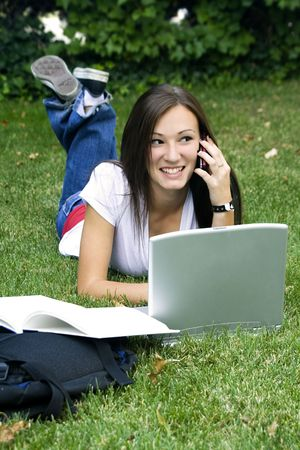 Cute teen girl laying down on the grass studying with her laptop Stock Photo - 3898241