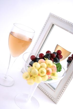 Isolated Grapes In a Glass in front of a Mirror with a Glass of Wine