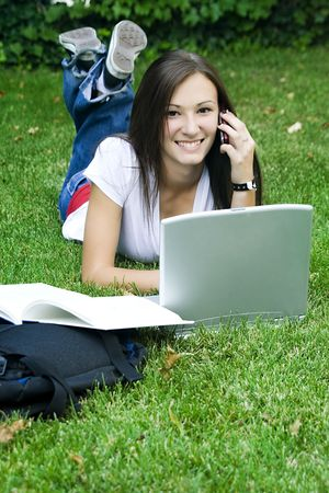 Cute teen girl laying down on the grass studying with her laptop Stock Photo - 4021352