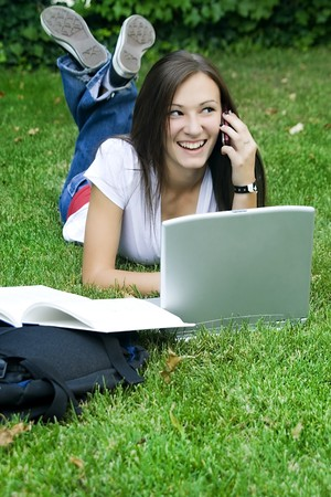 Cute teen girl laying down on the grass studying with her laptop Stock Photo - 4039269