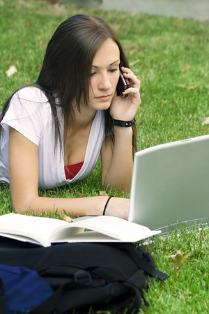 Cute teen girl laying down on the grass studying with her laptop Stock Photo - 4066591