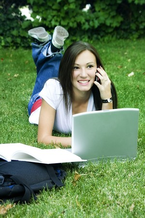 Cute teen girl laying down on the grass studying with her laptop Stock Photo - 4121141