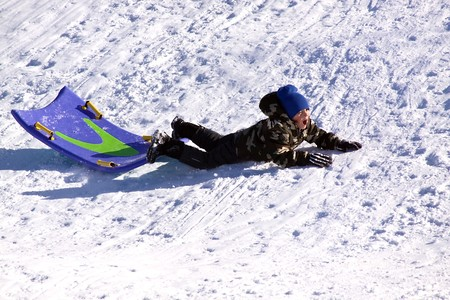 Little Boy Falling While Sledding down the Hill - Winter Scenes photo