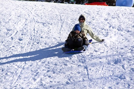 Mother and Son Sledding down the Hill - Winter Scenes photo