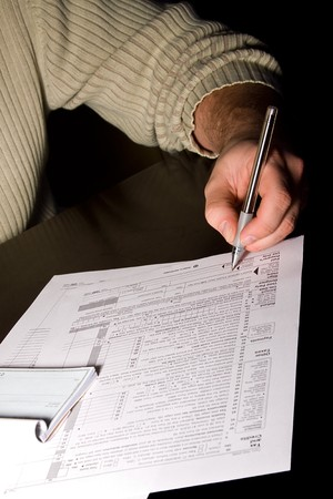 A man signing 1040 tax forms photo