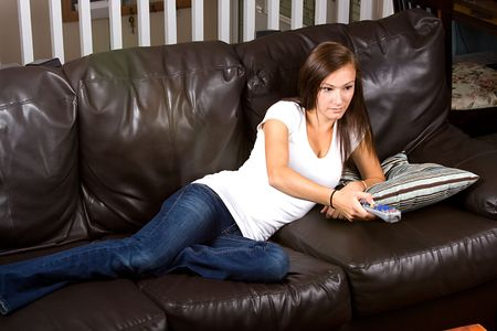 Girl at Home watching tv with a remote control  photo