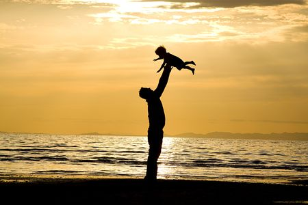 living together: Father throwing his kid up in the air on the beach Stock Photo