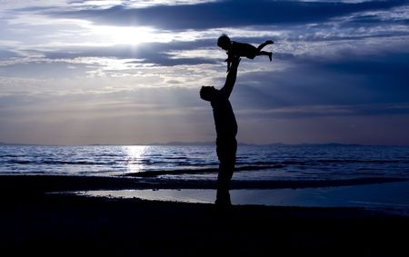 Father throwing his kid up in the air on the beach photo