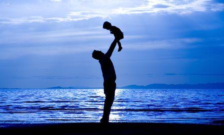 Vater wirft sein Kind in die Luft am Strand Standard-Bild