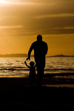 Father playing with his son on the beach photo