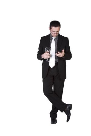Isolated businessman celebrating with a glass of drink while texting on his cell phone photo